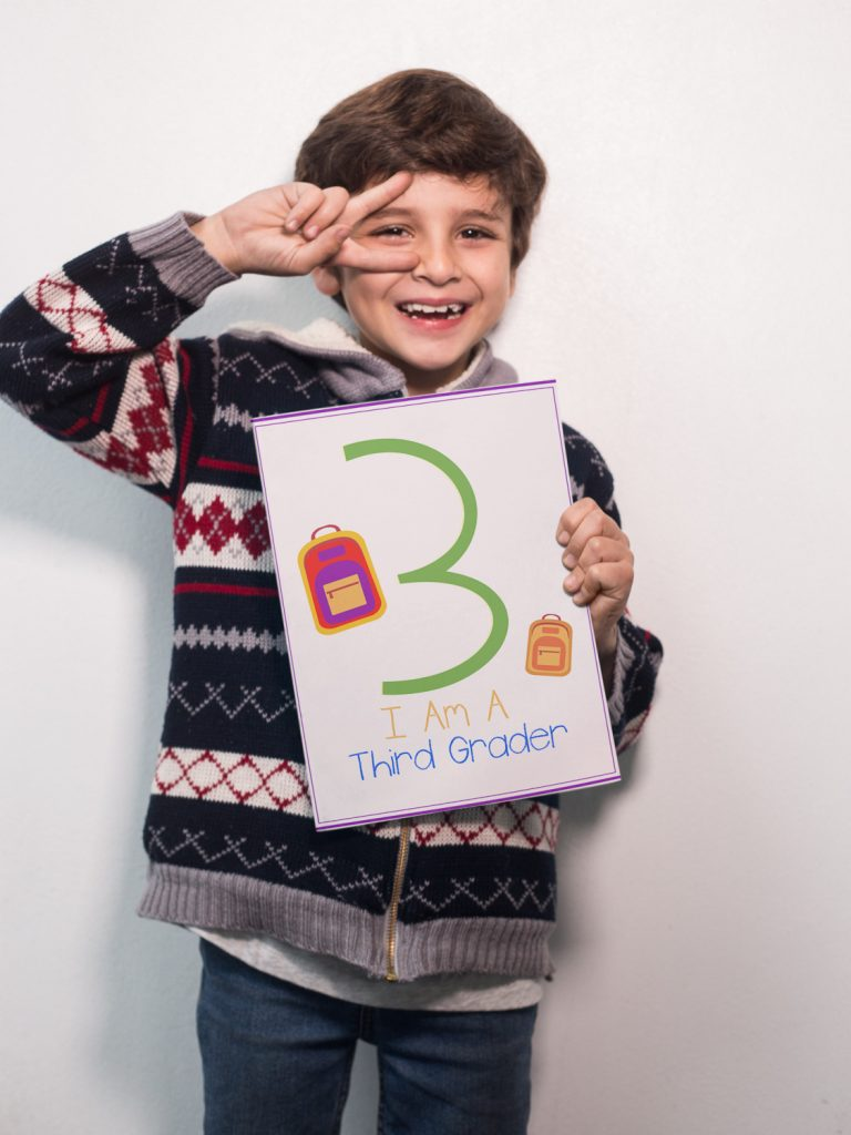 boy soing the peace sign holding Printable First Day of School Signs