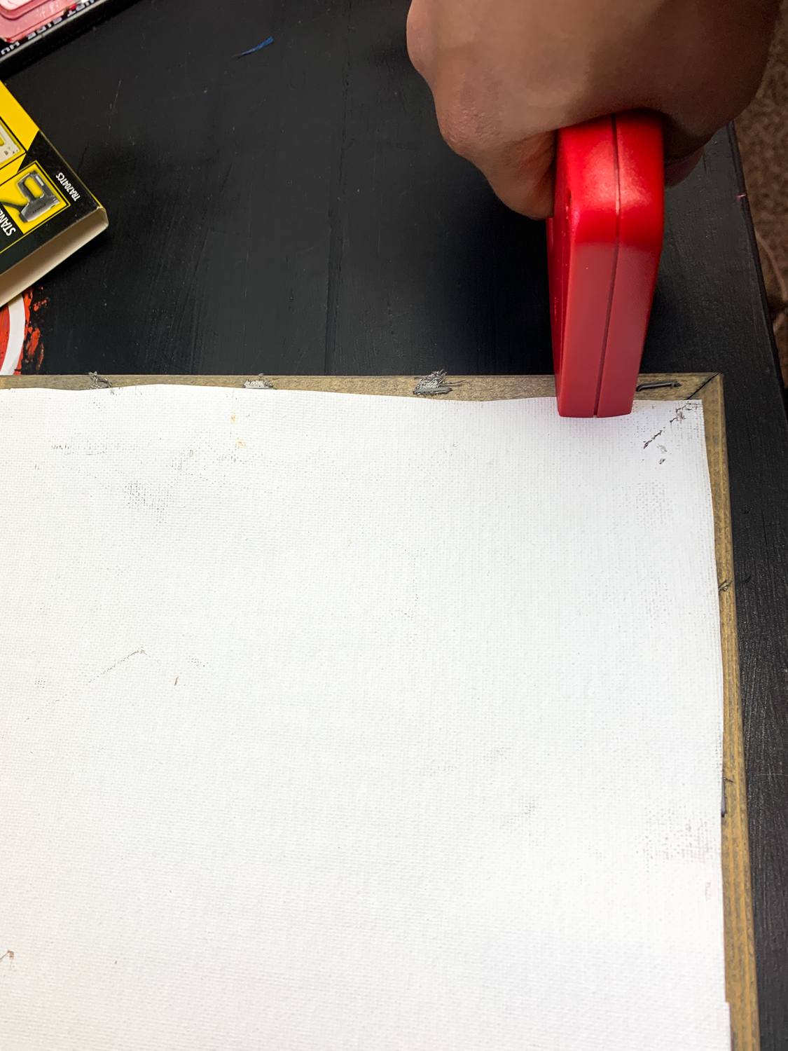 red staple gun, stapling the back of a reverse canvas