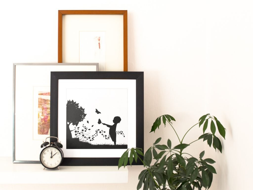 square framed wall art print near other art prints and a clock with diy artwork of a child with butterflies next to a tree
