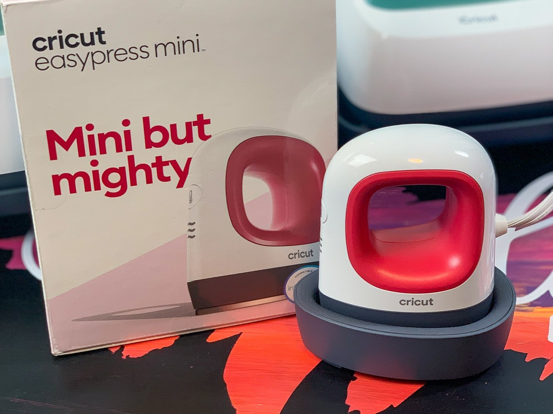 An image of the Cricut EasyPress Mini outside of the box, beside its original box.