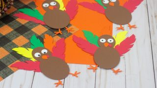 orange and black buffalo plaid cardstock with paper turkey craft laying on it