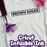 Infusibile Ink Baby Onesie on a table with text which reads cricut infusible ink baby onesie tutorial