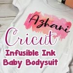 Infusible Ink Baby Onesie on a table with text which reads cricut infusible ink baby bodysuit