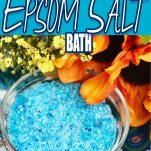 overhead view of a bowl of epsom salts colored blue with text which reads how to make your own epsom salts bath