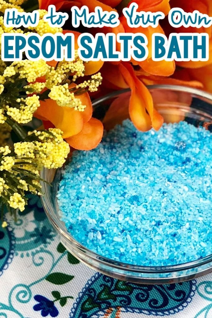 overhead view of a bowl of blue handmade epsom salts with text which reads how to make your own epsom salts bath
