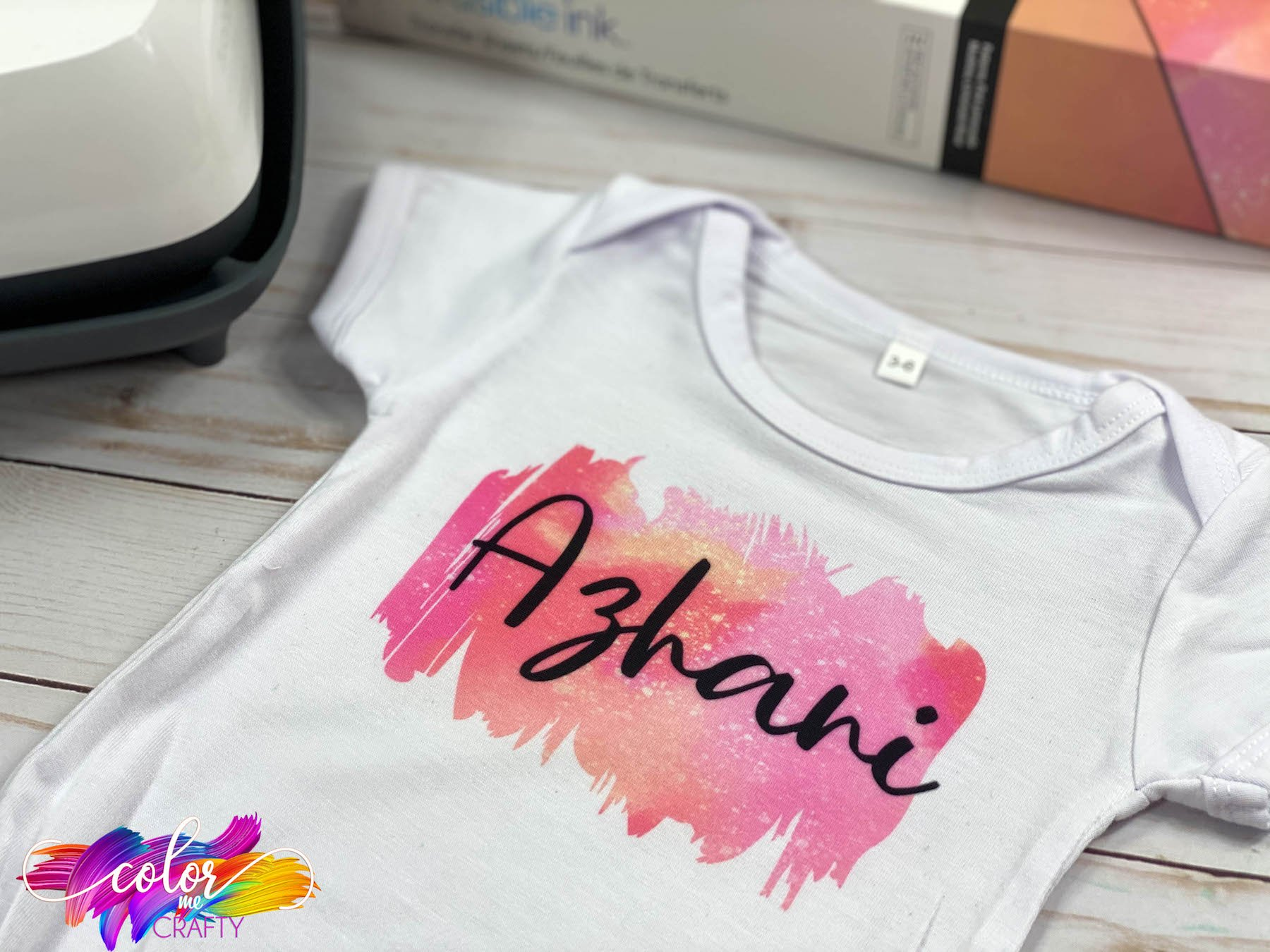 water color baby shirt with pink and yellow and black.