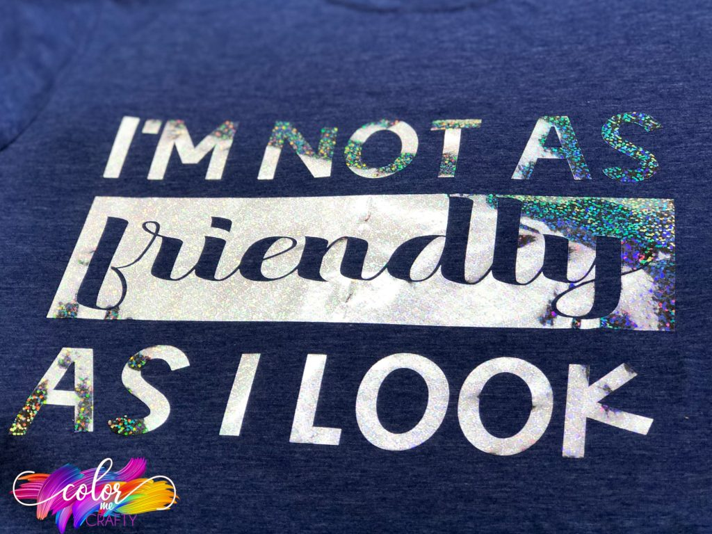 blue shirt with holographic iron on vinyl that says I'm not as friendly as I look