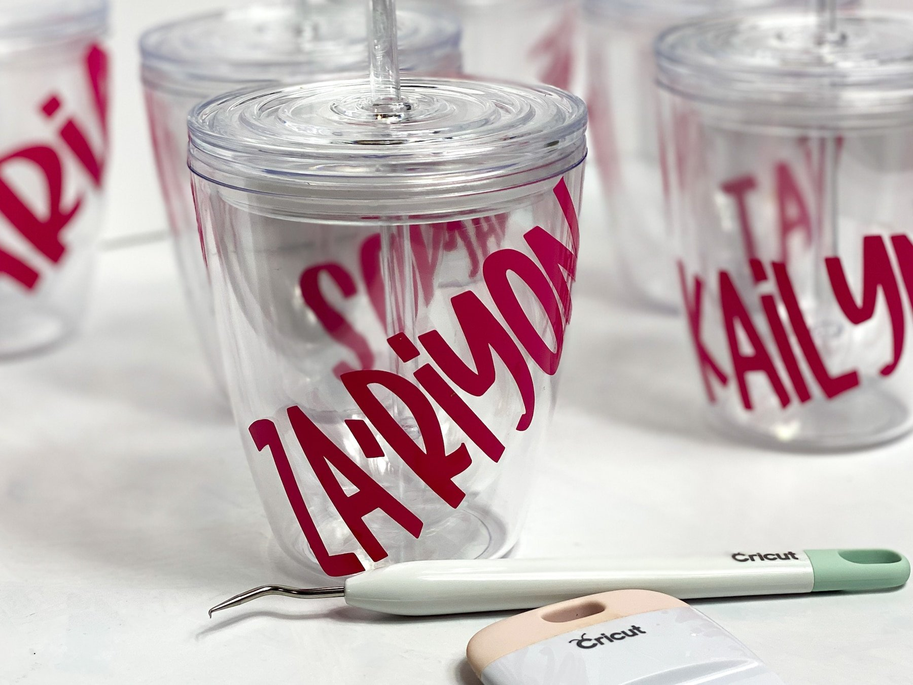 Clear Cricut cups with pink names, with a weeding tool and scraper in front