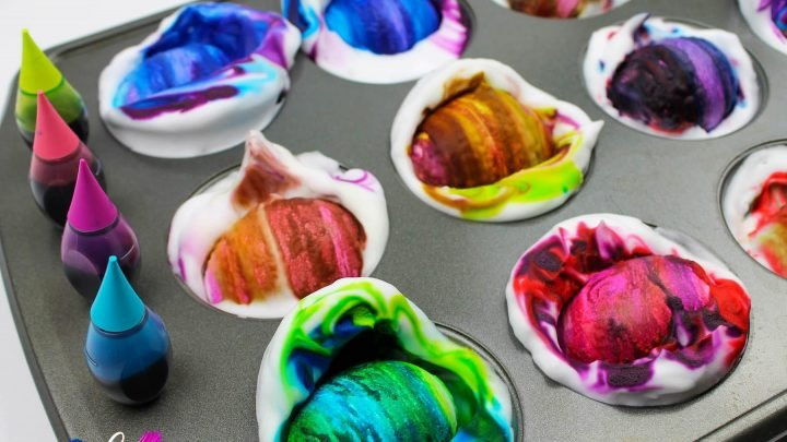 muffin tin full of shaving cream easter eggs being dyed various colors