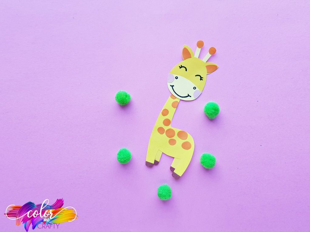 paper giraffe on purple background with green poms