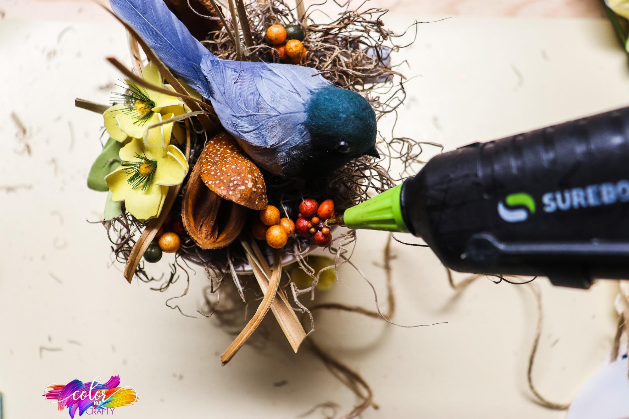 hot glue being applied to hold together DIY bird nest centerpiece