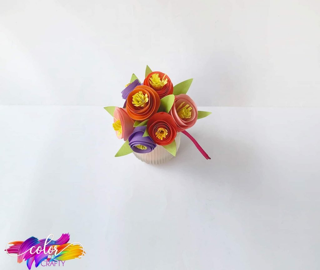 top view of bouquet of construction paper flowers on plain backdrop