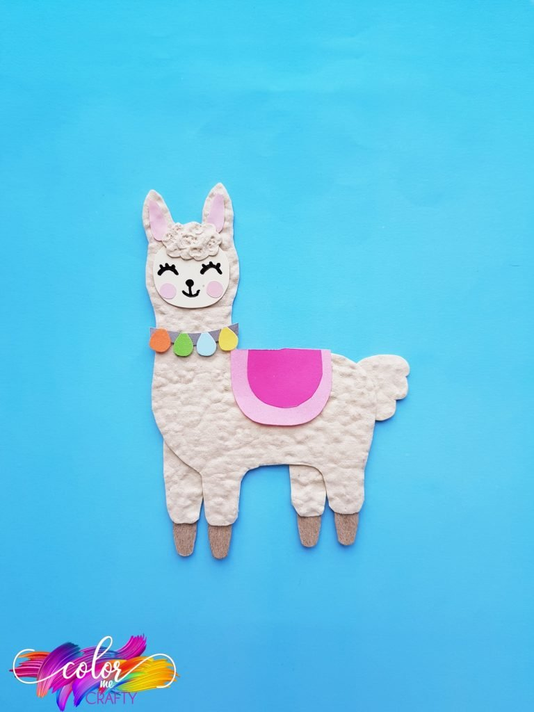 smiling paper llama on blue background