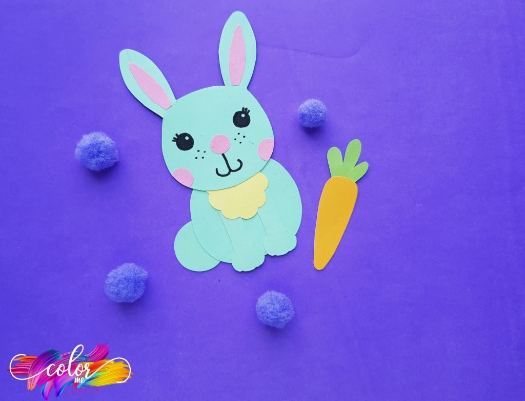 paper bunny with blue poms and orange carrot