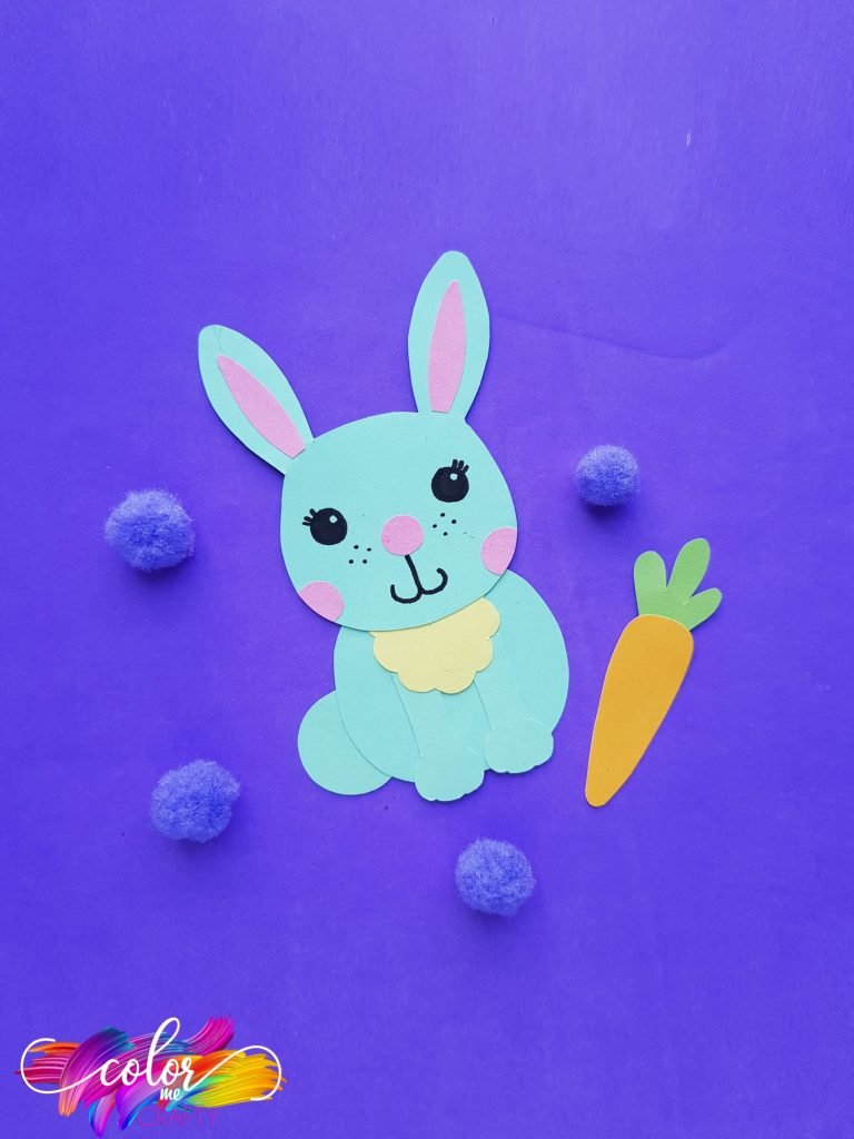 paper bunny on blue background with blue poms and paper carrot