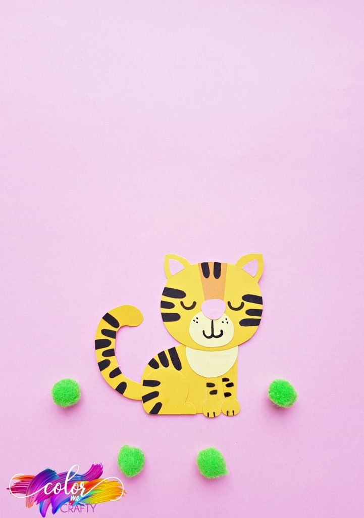 paper tiger on pink background with green poms