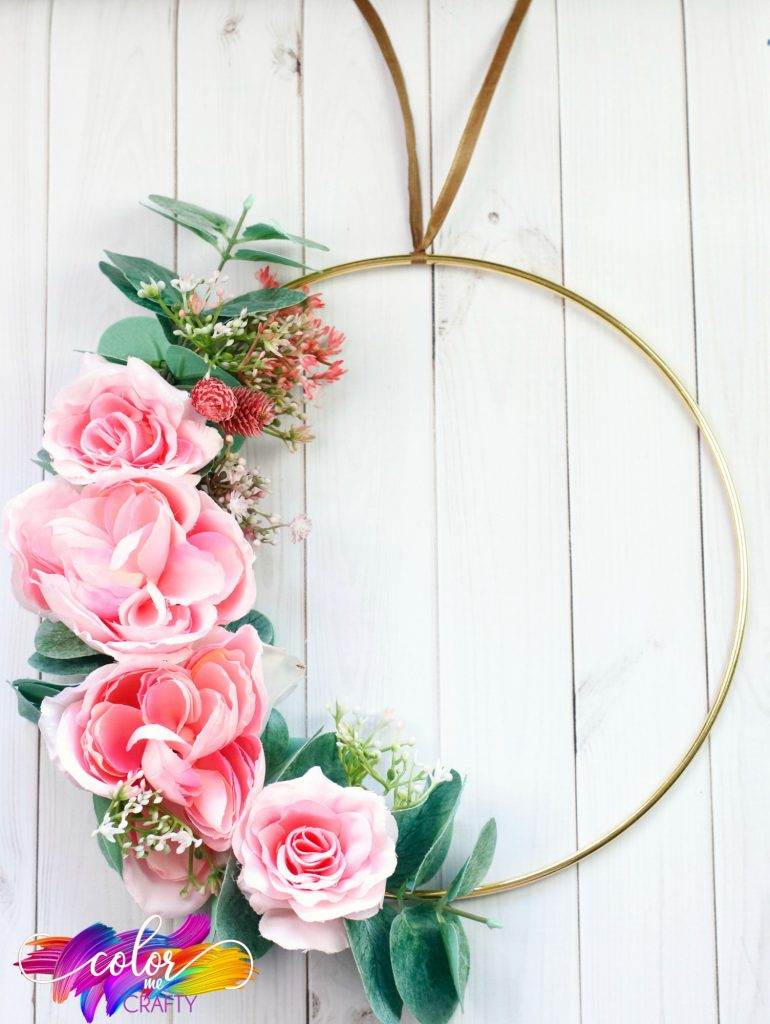 flower covered wreath hung with ribbon