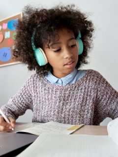 Smart african mixed race kid girl wearing headphones listening lesson learning online computer doing homework at home. Cute black child studying distance school education writing notes sitting at desk