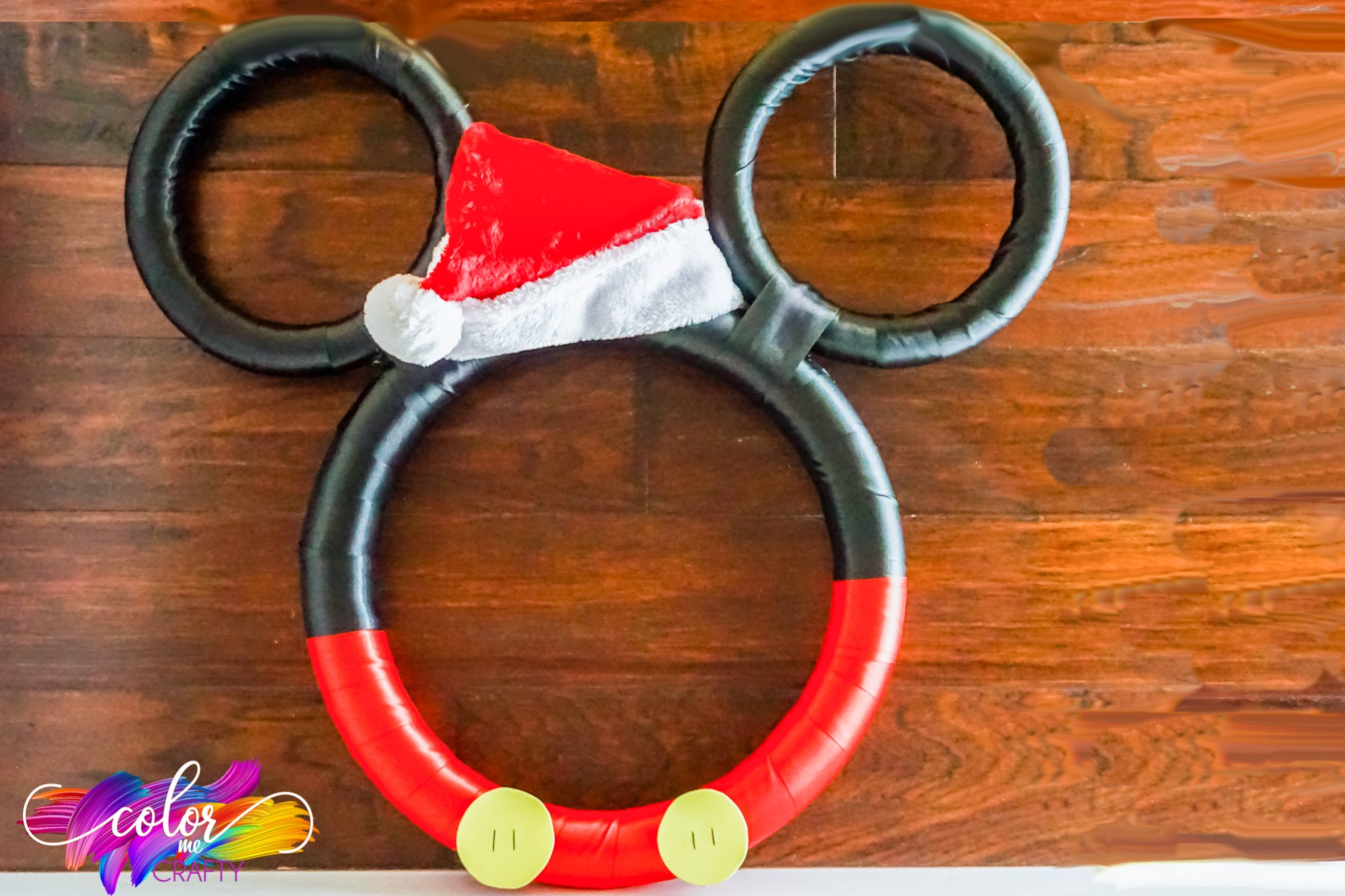 mickey mouse wreath with a christmas hat and two buttons on the bottom. Red lining for his pants at the bottom and black for his head and ears