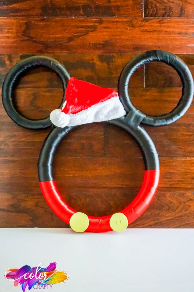 mickey mouse Christmas wreath with red on the bottom and black on the top. In between the ears is a red Santa hat. There are two yellow buttons at the bottom of the wreath