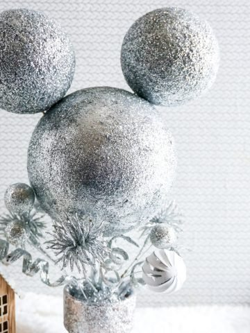 mickey mouse centerpiece with silver glitter all over. the base is a flower pot also coated in silver glitter