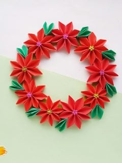 paper flower with red petals, green leaves, and colored dots in the center of the flowers