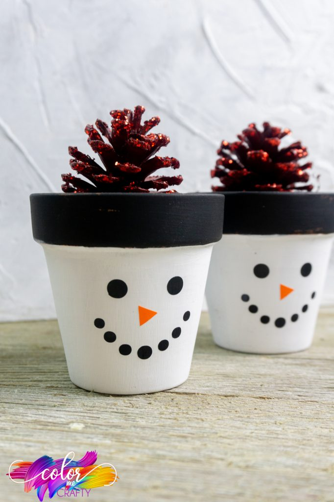 snowman planter with a white base and a pine-cone in the vase