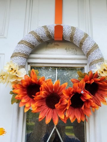 wreath with orange sunflowers and leaves in between the flowers