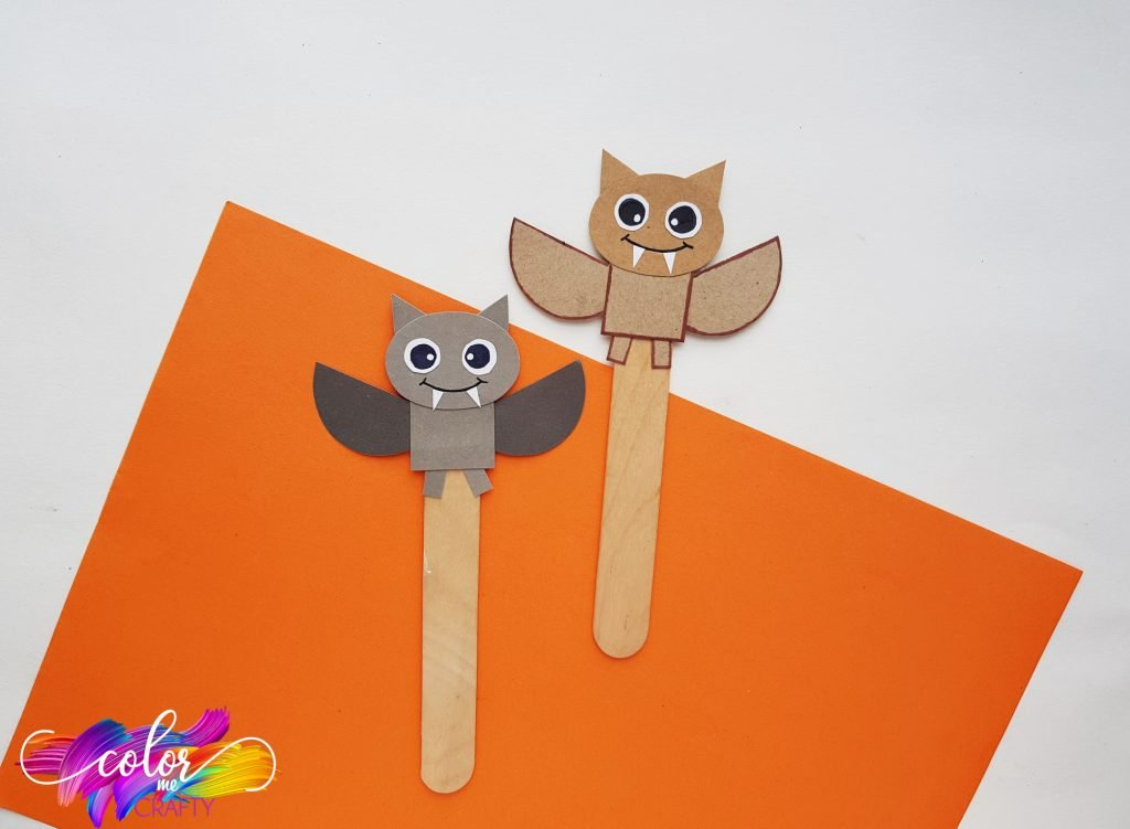 paper bat bookmark with gray and brown bats with cute faces and fangs. all on a popsicle stick