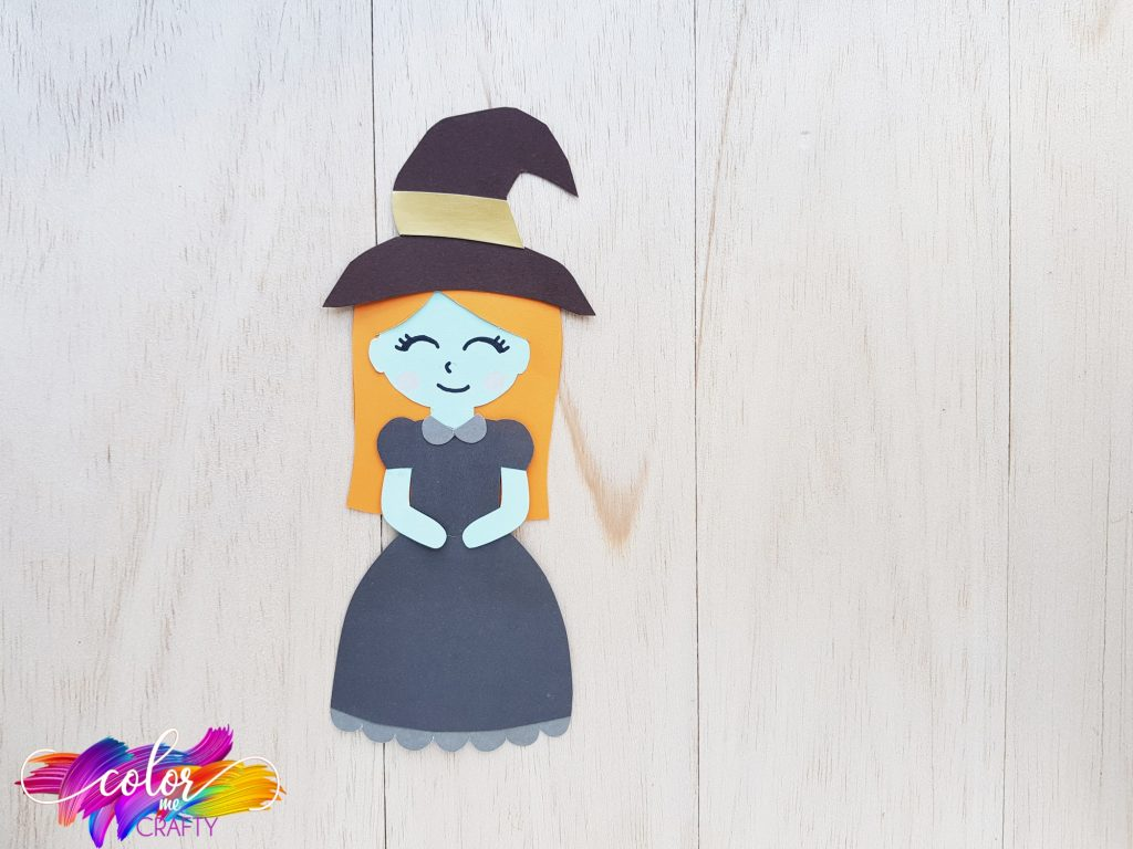 smiling paper witch with a black hat and black dress