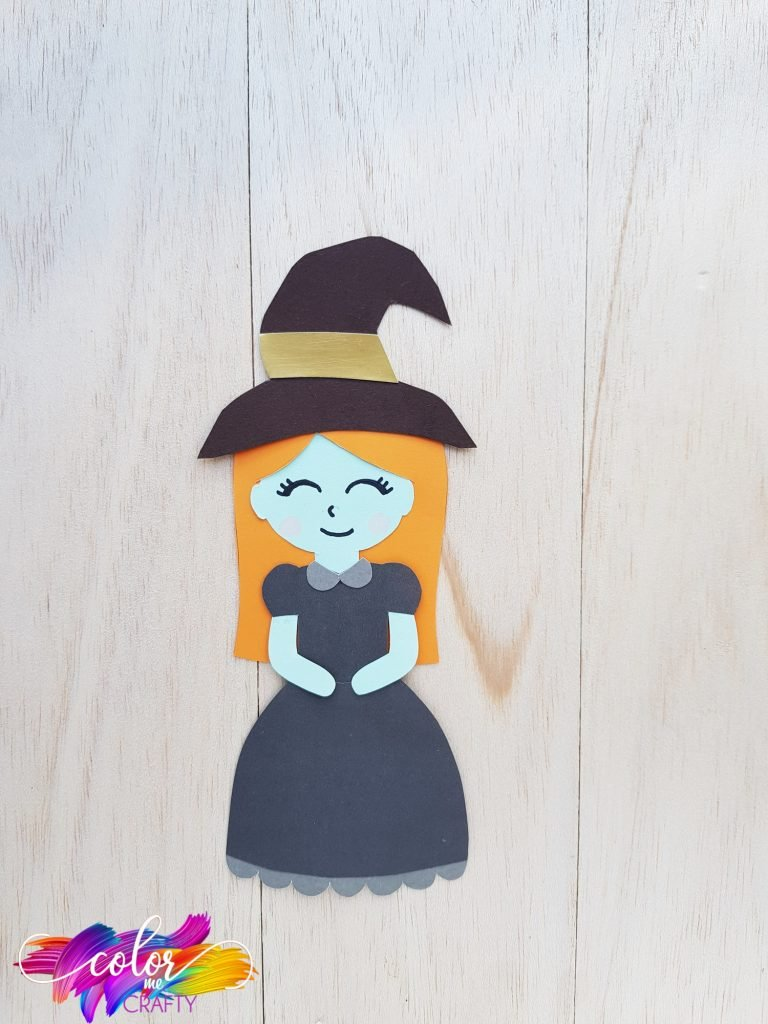 witch paper craft with black dress, black hat, orange hair, and a smiling face on a light wooden background