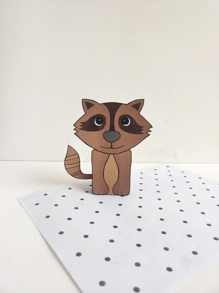 paper raccoon made with an empty toilet paper roll on top of a sheet of polka dot paper
