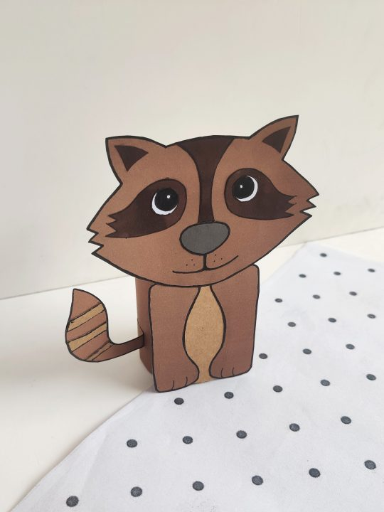 smiling brown paper raccoon made form an empty toilet paper roll with nude background