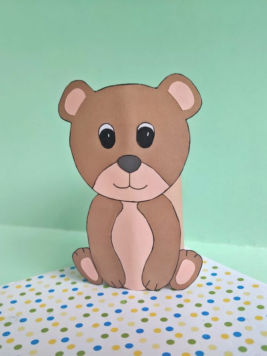 brown bear made with construction paper and an empty toilet paper roll. the background is green and there are green polka dots under the bear
