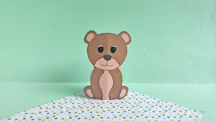 bear made from toilet paper roll and brown construction paper on a green background and a polka dotted sheet of paper below it