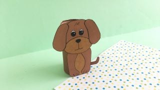 cute brown dog made with toilet paper roll with green background