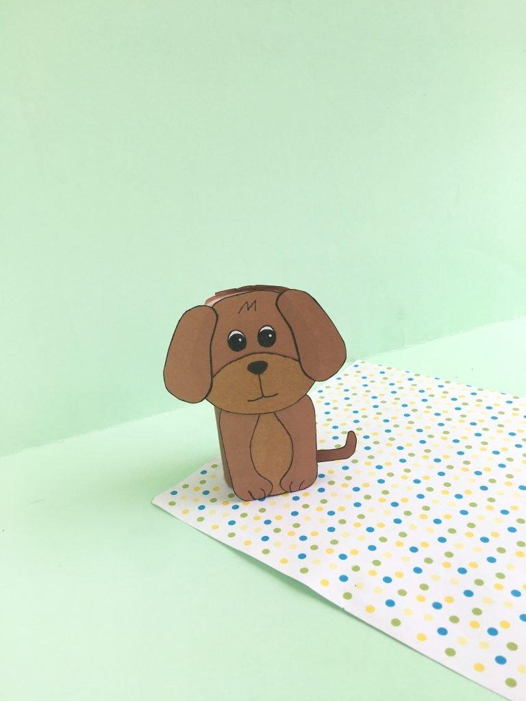 toilet paper roll made into paper dog with a green background