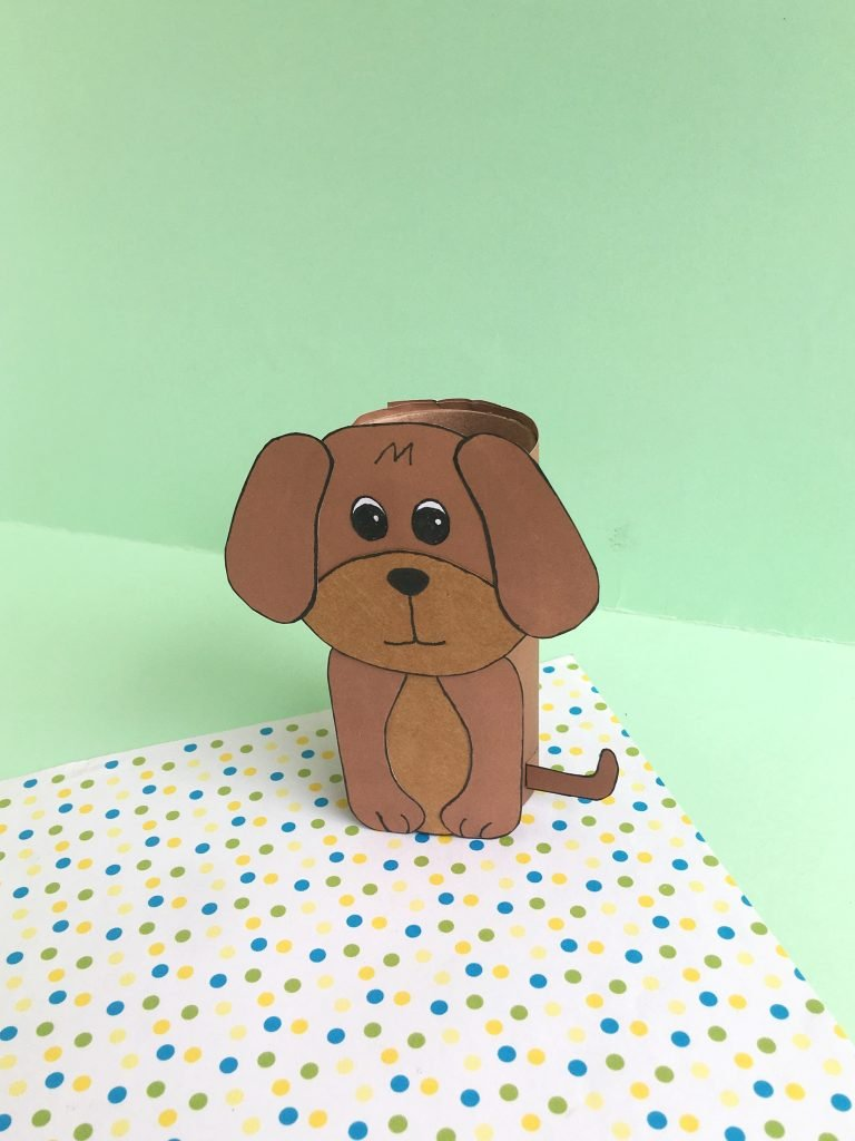 paper dog made from brown colored paper and empty toilet paper roll with green background