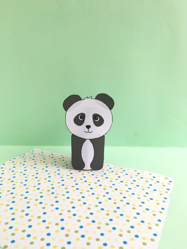 black and white paper panda made with toiler paper roll on green background and polkadots