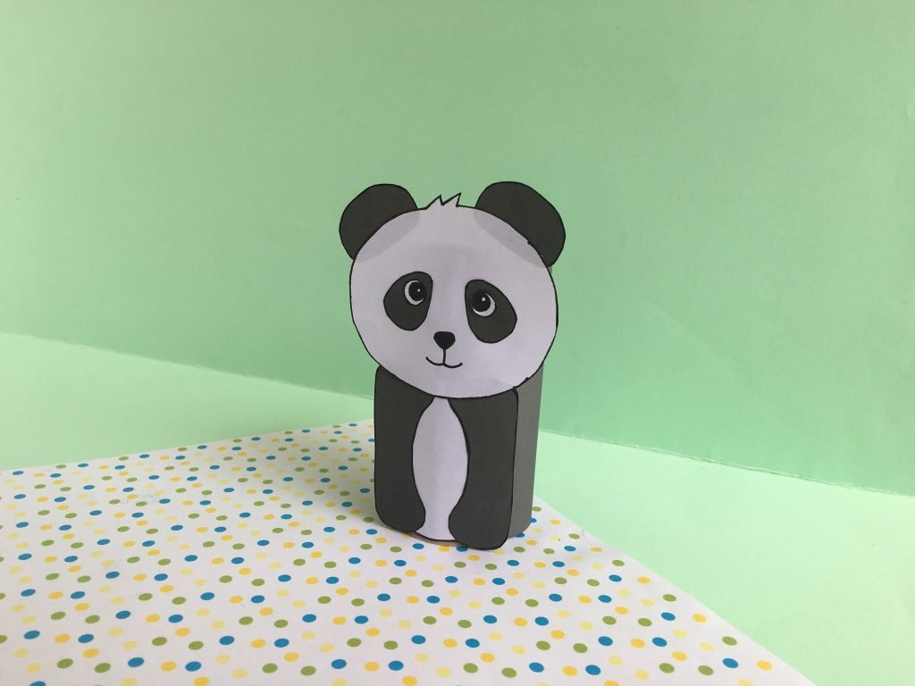 paper panda made with an empty toilet paper roll. the panda is black and white and the photo has a green background with polka dots at the bottom