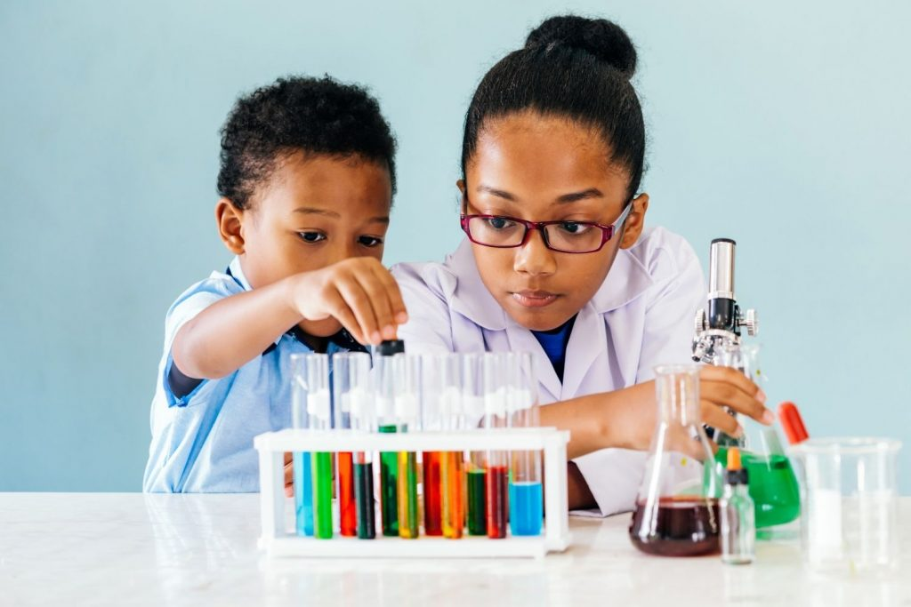 black boy in a blue shirt doing a science experiment with a black girl in glasses and a lab coat
