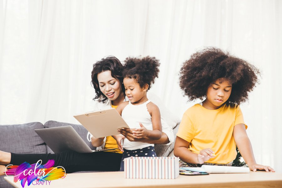 mother and daughter working on clipboard while sitting on a couch finding the child's best learning method while other daughter works on homework