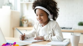 child in white shirt and wearing white headphones smiling as she works and has nice transition to homeschool with notebooks in front of her and pencil in hand