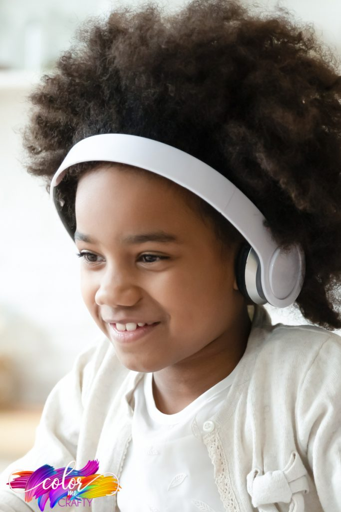 child in white shirt and wearing white headphones smiling as she works and has nice transition to homeschool