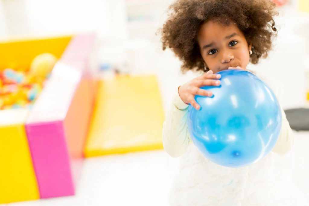 blackchild with an afro holding a blue balloon