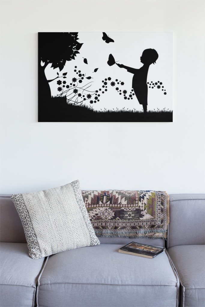 silhouette of a child playing with butterfly on a canvas above a couch.