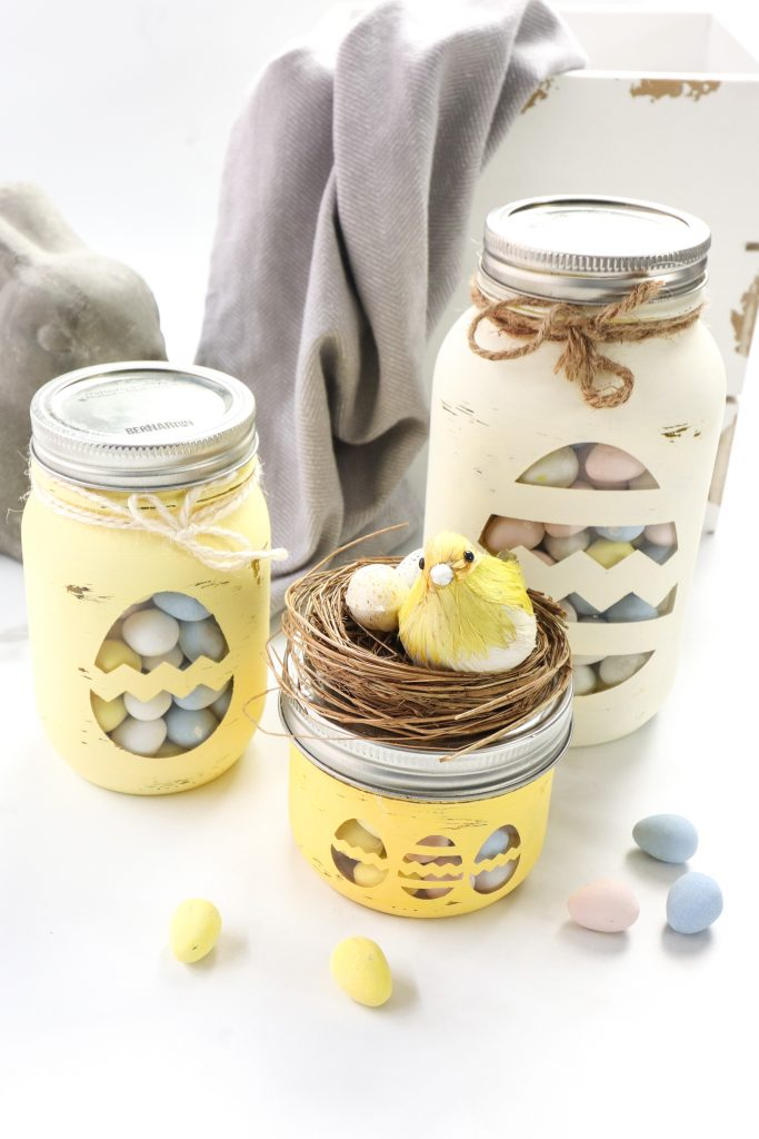 chalky painted mason jars for Easter; light yellows, pinks, and blues for the eggs, twine tied around the lid; egg cut out shapes on the front