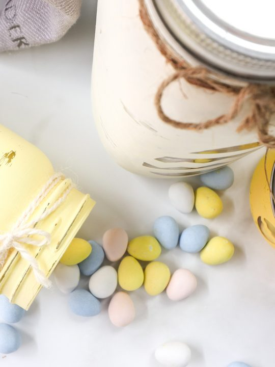 chalky painted mason jars for Easter; light yellows, pinks, and blues for the eggs, twine tied around the lid; egg cut out shapes on the front; eggs spilling out of sideways jar