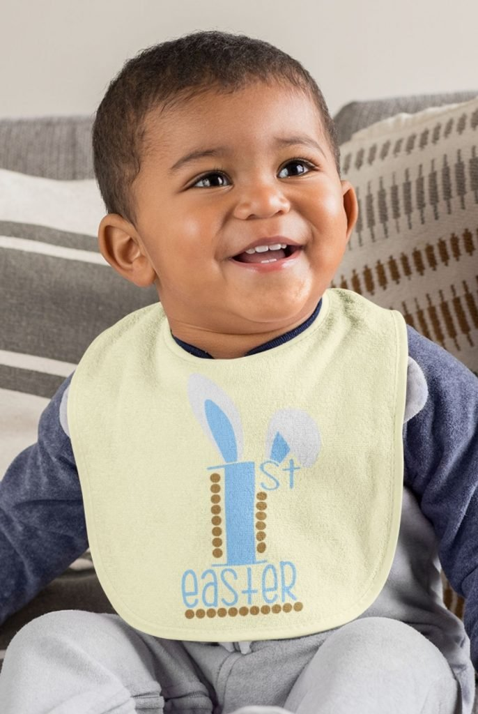 smiling baby in a yellow bib with blue babys first easter design on it