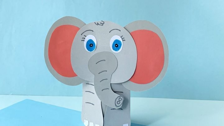 paper elephant with pink ears and blue eyes. light blue background
